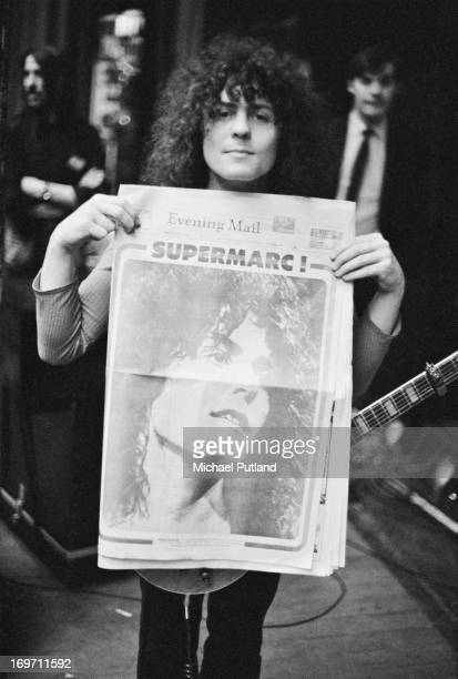 Marc Bolan of English glam rock group TRex holding up a copy of the Birmingham Evening Mail whose front page is given over to a portrait of the...