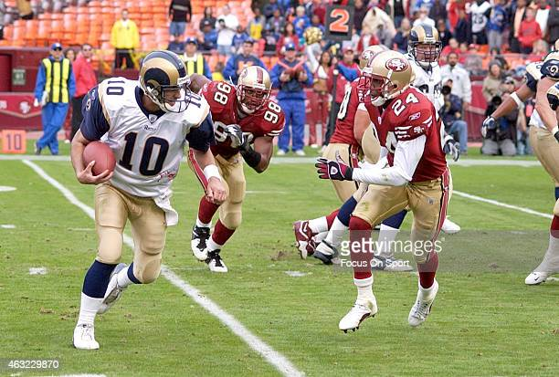 Marc Bulger of the St Louis Rams scrambles away from the pursuit of Mike Rumph of the San Francisco 49ers during an NFL Football game November 2 2003...