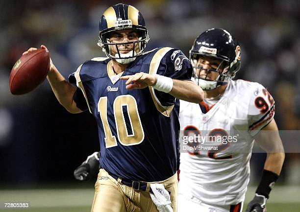Marc Bulger of the St Louis Rams throws for a touchdown as Hunter Hillenmeyer of the Chicago Bears pursues at the Edward Jones Dome December 11 2006...