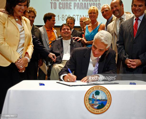 Marc Buoniconti center smiles as Gov Charlie Crist ceremonially signs the bill HB 325 into law Mary Anne Shula left and State Sen Thad Altman right...