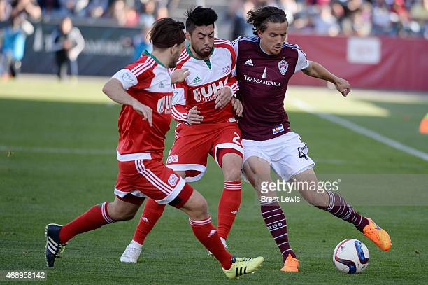 Marc Burch of Colorado Rapids is bumped by Lee Nguyen of New England Revolution and Kelyn Rowe of New England Revolution during the first half...
