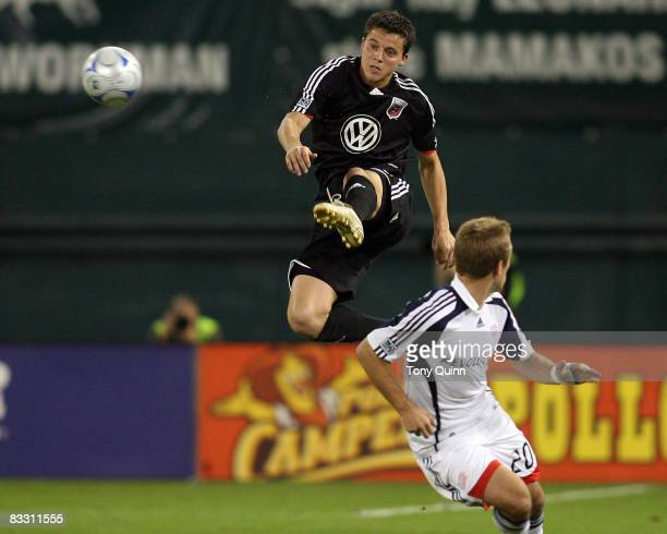 Marc Burch of DC United leaps high to clear the ball from Taylor Twellman of New England Revolution during an MLS match at RFK Stadium on October 16...