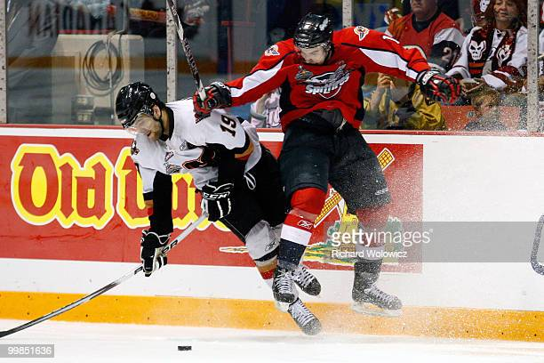 Marc Cantin of the Windsor Spitfires body checks Ian Schultz of the Calgary Hitmen during the 2010 Mastercard Memorial Cup Tournament at the Keystone...