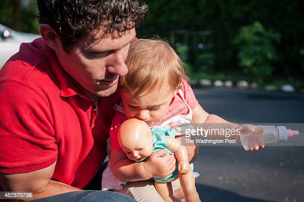 Marc Carlson holds 14-month-old daughter Rebecca as he teaches her to feed her doll with a bottle. Marc, a senior manager at Ernst & Young, took...