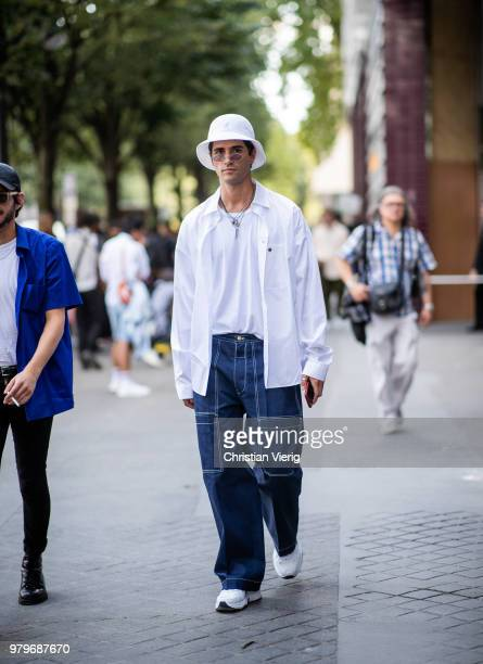 Marc Forne wearing white bucket hat baggy denim jeans white button shirt and tshirt is seen outside Acne on day two of Paris Fashion Week Menswear...