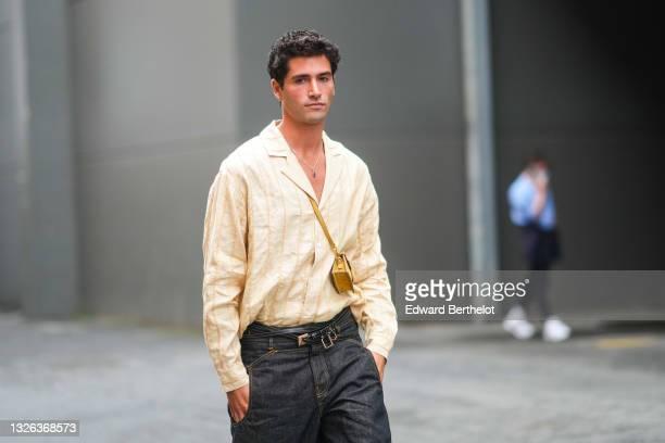"""Marc Forne wears a pale yellow striped shirt, a crossbody Jacquemus bag, a leather belt, black jeans, during Jacquemus """"La Montagne"""" Show, at La Cite..."""