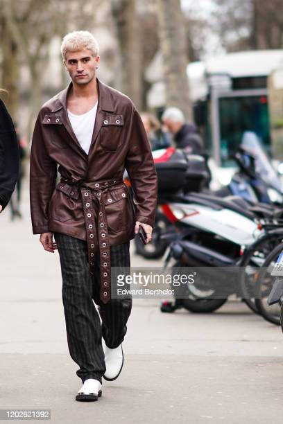 Marc Forne wears a white top, a dark brown leather jacket with eyelets, grey and navy-blue striped pants, white boots, during Paris Fashion Week -...