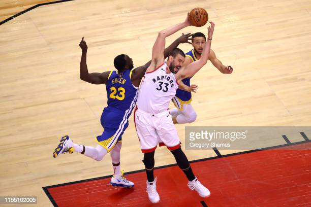 Marc Gasol of the Toronto Raptors battles for the ball with Draymond Green and Stephen Curry of the Golden State Warriors in the first half during...