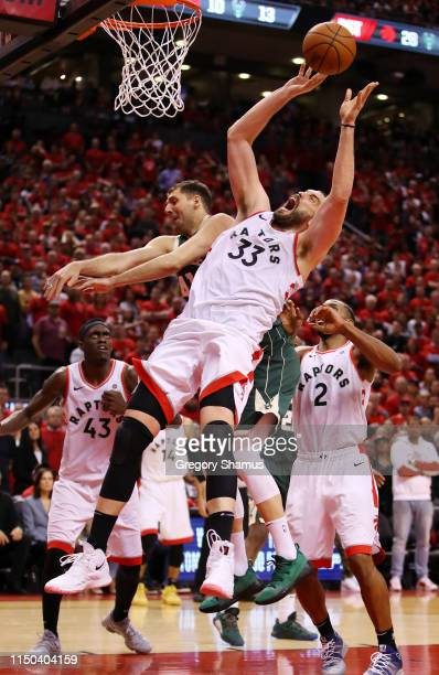 Marc Gasol of the Toronto Raptors shoots the ball against Nikola Mirotic of the Milwaukee Bucks during overtime in game three of the NBA Eastern...