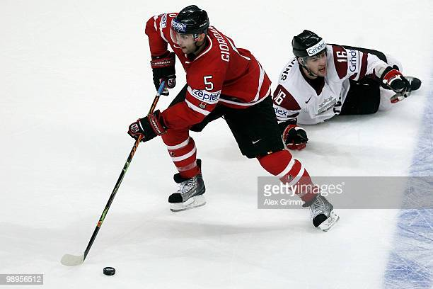 Marc Giordano of Canada eludes Kaspars Daugavins of Latvia on his way to score his team's fourth goal during the IIHF World Championship group B...