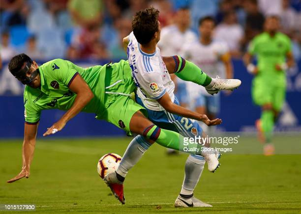 Marc Gual of Real Zaragoza is tackled by Chema of Levante during the friendly match between Real Zaragoza and Levante UD at La Romareda on August 11...