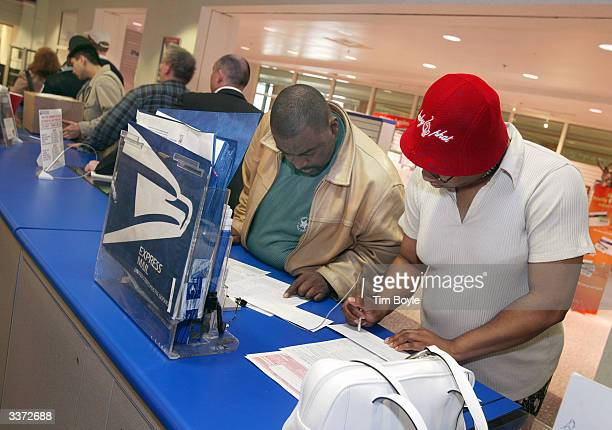 Marc Holiday and Karen McGhee fills out income tax extension applications while in line at the main post office April 15 2004 in Chicago Illinois...