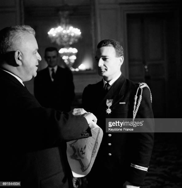 Marc Jacquet remet au lieutenant de vaisseau Eric Tabarly la croix de chevalier de l'ordre du mérite maritime au ministère des travaux publics à...