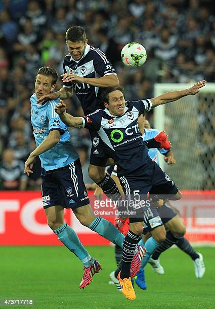 Marc Janko of Sydney FC Carl Valeri and Mark Milligan of Melbourne Victory compete in the air during the 2015 ALeague Grand Final match between the...
