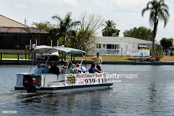 Marc Joseph the owner of Foreclosures 'R Us realty company talks from the front of a boat to prospective buyers as they motor down a canal during a...