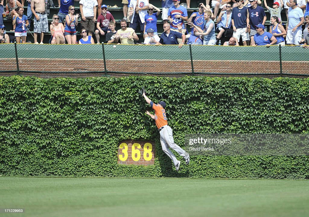 Marc Krauss #59 of the Houston Astros can't catch a triple off the bat of Luis Valbuena #24 of the Chicago Cubs during the seventh inning on June 23, 2013 at Wrigley Field in Chicago, Illinois.