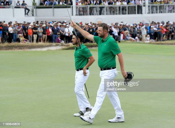 Marc Leishman and Abraham Ancer of the International Team celebrate as the leave the 16th green after winning their match against Webb Simpson and...