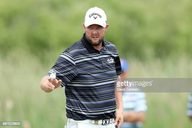 Marc Leishman of Australia acknowledges the crowd after making a birdie at the par 5 first hole during the third round of the 117th US Open...