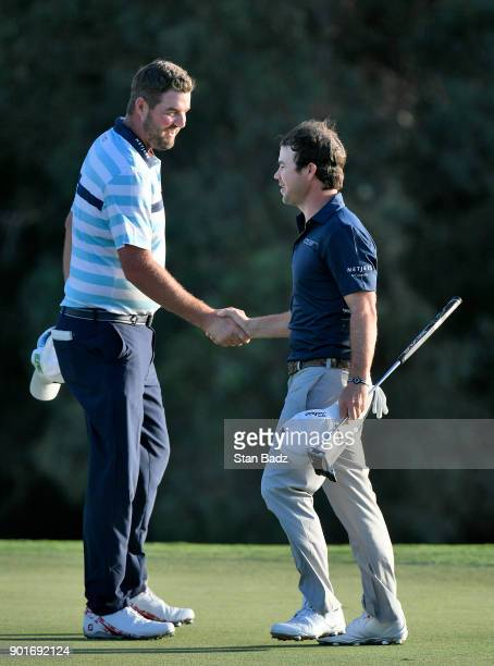 Marc Leishman of Australia and Brian Harman of the United States shake hands after finishing on the 18th green during the second round of the Sentry...