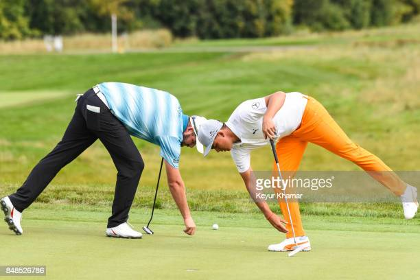 Marc Leishman of Australia and Rickie Fowler repair divots on the seventh hole green during the final round of the BMW Championship at Conway Farms...