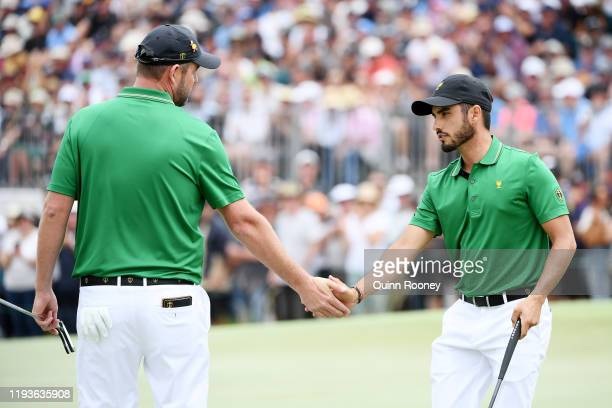 Marc Leishman of Australia and the International team and Abraham Ancer of Mexico and the International team celebrate on the 14th green during...