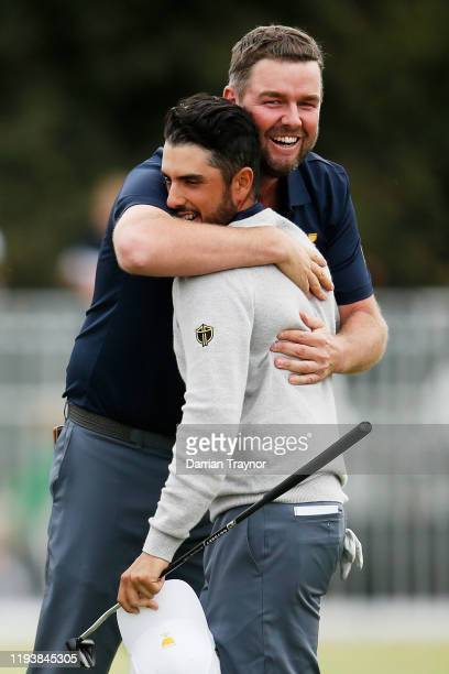 Marc Leishman of Australia and the International team and Abraham Ancer of Mexico and the International team celebrate after halving their match...