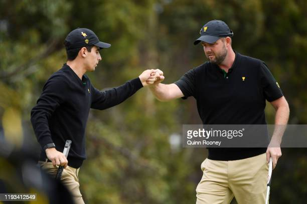 Marc Leishman of Australia and the International team celebrates with Joaquin Niemann of Chile and the International team on the 12th green during...