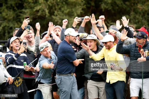 Marc Leishman of Australia and the International team celebrates with fans after his shot on the 18th hole during Saturday afternoon foursomes...