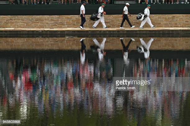 Marc Leishman of Australia and Tiger Woods of the United States cross the Sarazen Bridge on the 16th hole during the second round of the 2018 Masters...