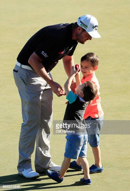 Marc Leishman of Australia celebrates with his children Oliver and Harry after finishing on the 18th green during the final round of the Arnold...