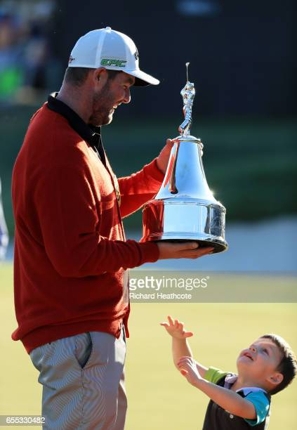 Marc Leishman of Australia celebrates with the trophy and one of his sons after finishing on the 18th green during the final round of the Arnold...