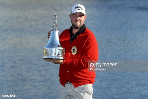 Marc Leishman of Australia holds the trophy wearing the Arnold Palmer commemorative red cardigan after his one shot victory in the final round of the...