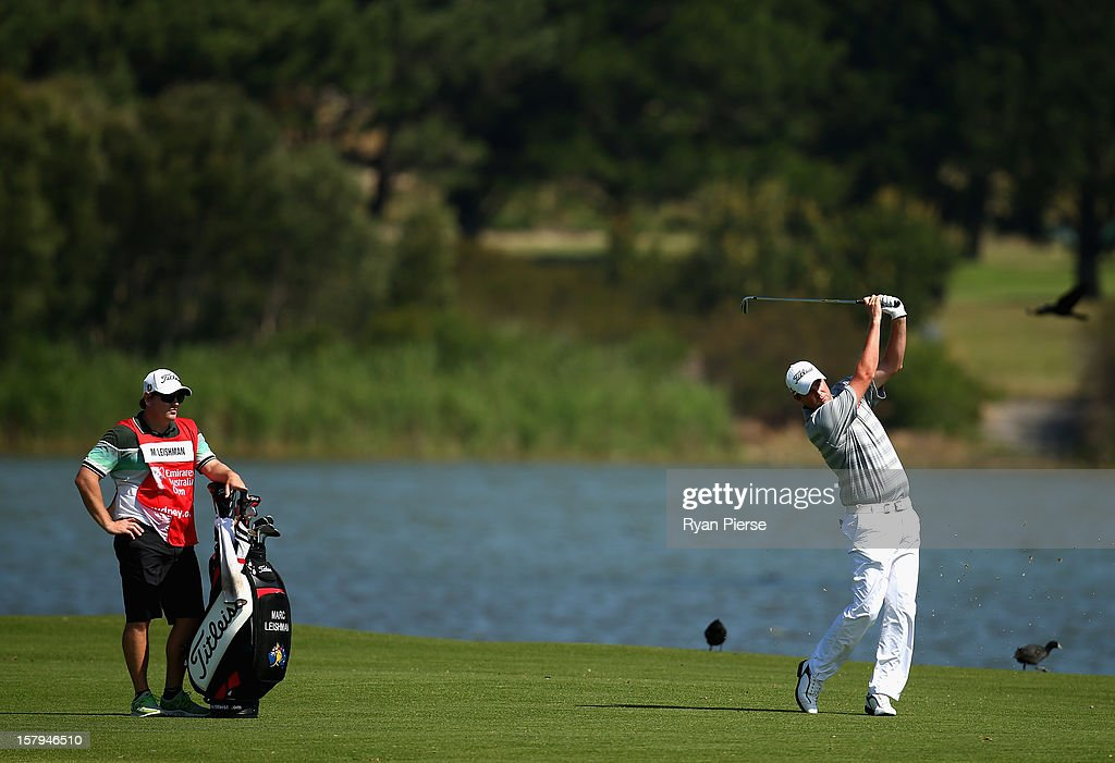 Marc Leishman of Australia plays a shot as his caddie Matt Kelly watches on during round three of the 2012 Australian Open at The Lakes Golf Club on December 8, 2012 in Sydney, Australia.