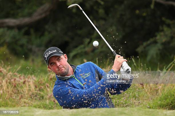 Marc Leishman of Australia plays out of the bunker during previews ahead of the 2013 Australian Masters at Royal Melbourne Golf Course on November...