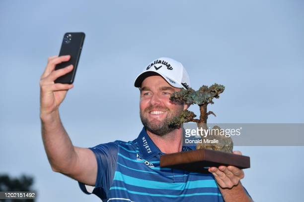 Marc Leishman of Australia poses with the Torrey Pines trophy after winning the final round of the Farmers Insurance Open at Torrey Pines South on...