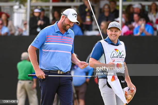 Marc Leishman of Australia smiles with his caddie Matty Kelly on the 17th hole green during the final round of the Arnold Palmer Invitational...
