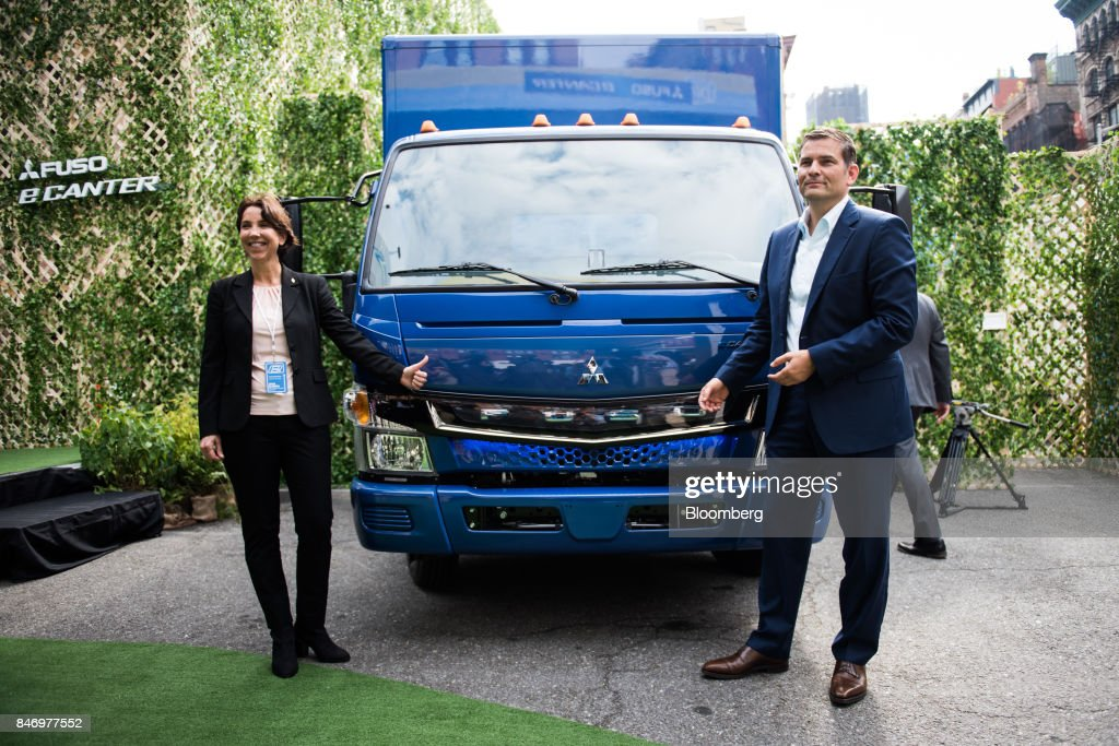 Marc Llistosella, chief executive officer of Mitsubishi Fuso Truck and Bus Corp., right, and Jecka Glasman, chief executive officer of Mitsubishi Fuso Truck of America Inc., stand for a photograph next to the eCanter truck during a launch event in New York, U.S., on Thursday, Sept. 14, 2017. The Daimler AG unit unveiled the new Fuso eCanter, an electric light-duty truck produced under its Mitsubishi Fuso brand. The latest version has a range of 60 to 80 miles (97 to 129 kilometers) between charges, depending on body, load and usage. Photographer: Mark Kauzlarich/Bloomberg via Getty Images