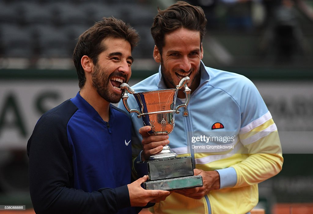 Marc Lopez and Feliciano Lopez of Spain celebrate with the trophy following their victory during the Men's Doubles final match against Mike Bryan and Bob Bryan of the United States on day fourteen of the 2016 French Open at Roland Garros on June 4, 2016 in Paris, France.