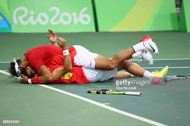 Marc Lopez of Spain and Rafael Nadal of Spain celebrate victory in their men's doubles semifinal against Daniel Nestor of Canada and Vasek Pospisil...