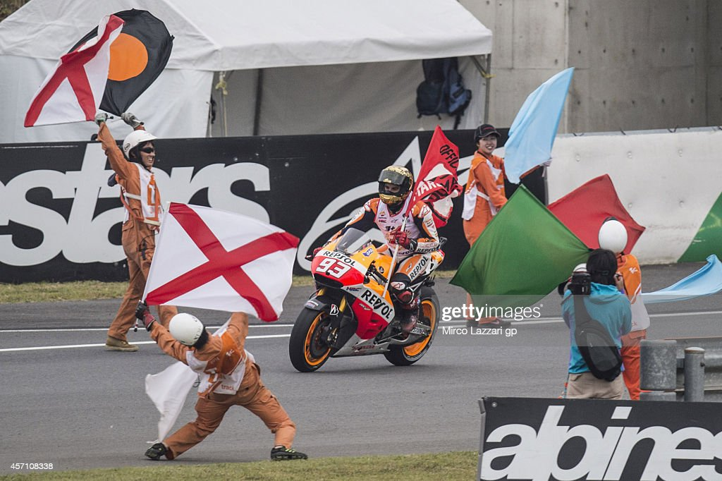 Marc Marquez of Spain and Repsol Honda Team celebrates with the flag the victory in the MotoGP championship at the end of the MotoGP race during the MotoGP Of Japan - Race at Twin Ring Motegi on October 12, 2014 in Motegi, Japan.