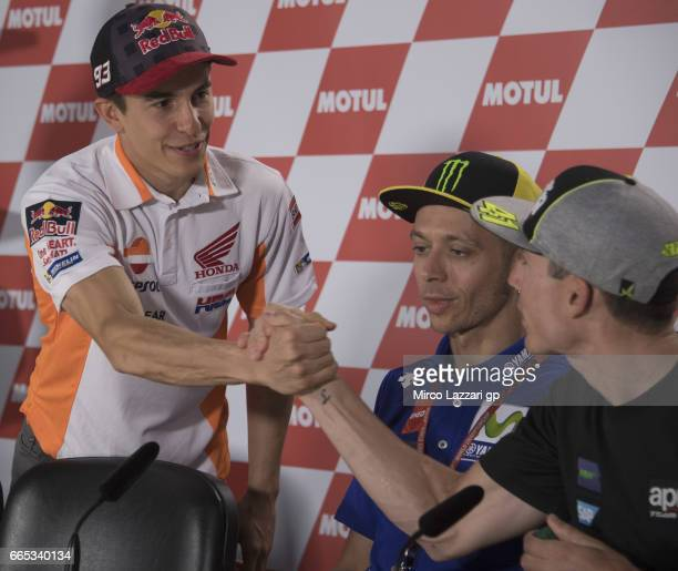 Marc Marquez of Spain and Repsol Honda Team greets Aleix Espargaro of Spain and Team Suzuki ECSTAR while Valentino Rossi of Italy and Movistar Yamaha...