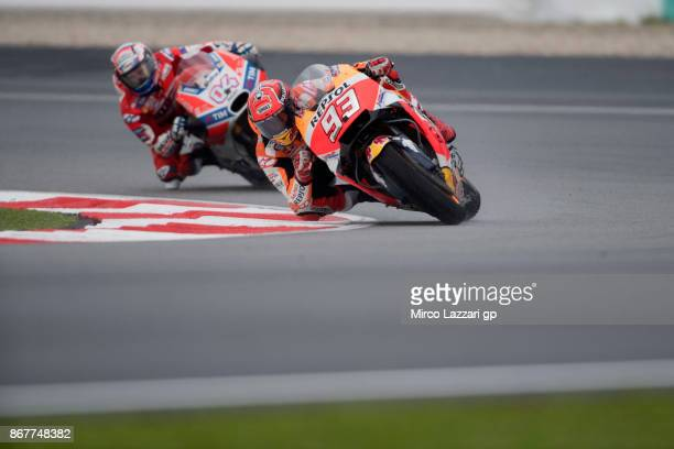 Marc Marquez of Spain and Repsol Honda Team leads Andrea Dovizioso of Italy and Ducati Team during the MotoGP race during the MotoGP Of Malaysia Race...