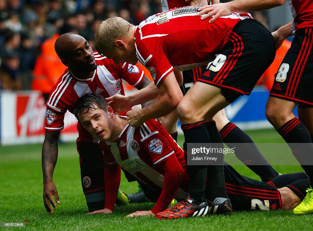 Marc McNulty of Sheffield United (2L) celebrates with team mates as he scores their first goal during the FA Cup Third Round match between Queens Park Rangers and Sheffield United at Loftus Road on January 4, 2015 in London, England.