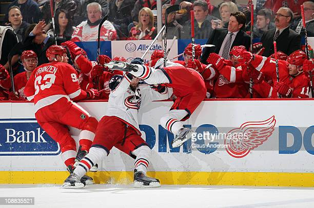 Marc Methot and Rick Nash of the Columbus Blue Jackets take each other out trying to hit Johan Franzen of the Detroit Red Wings in a game on February...