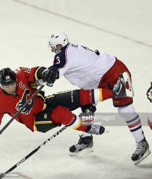 Marc Methot of the Columbus Blue Jackets dumps Jarome Iginla of the Calgary Flames at the Scotiabank Saddledome on December 1 2011 in Calgary Canada