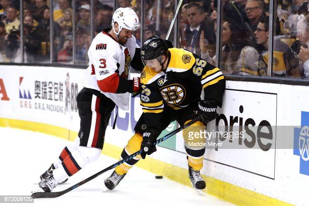 Marc Methot of the Ottawa Senators checks Noel Acciari of the Boston Bruins into the boards during the third period of Game Six of the Eastern...