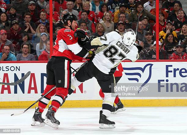 Marc Methot of the Ottawa Senators checks Sidney Crosby of the Pittsburgh Penguins at Canadian Tire Centre on April 7 2015 in Ottawa Ontario Canada