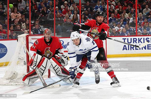 Marc Methot of the Ottawa Senators shoves David Clarkson of the Toronto Maple Leafs in front of goalie Craig Anderson of the Senators in the third...