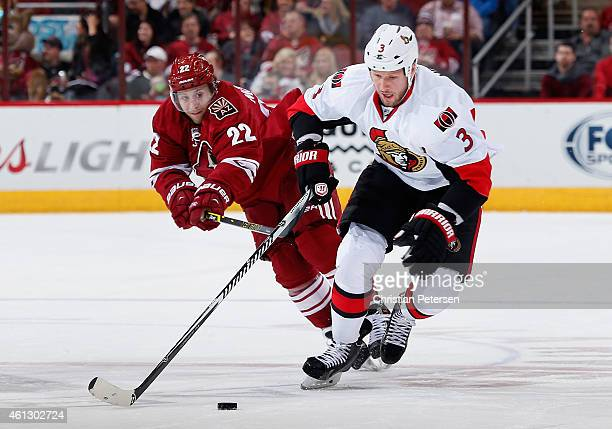 Marc Methot of the Ottawa Senators skates with the puck under pressure from Brandon McMillan of the Arizona Coyotes during the second period of the...