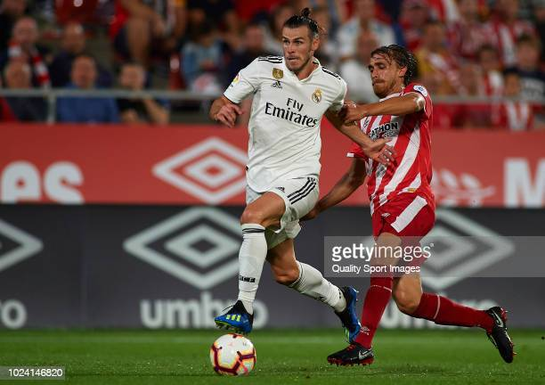 Marc Muniesa of Girona competes for the ball with Gareth Bale of Real Madrid during the La Liga match between Girona FC and Real Madrid CF at...